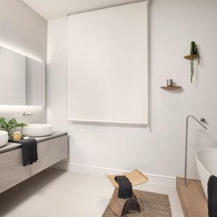 Diseño de cuarto de baño contemporáneo con armarios con paneles lisos, puertas de armario grises, paredes blancas, lavabo sobreencimera, suelo gris y encimeras grises