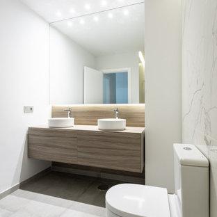 Foto de cuarto de baño con ducha, actual, de tamaño medio, con armarios con paneles lisos, puertas de armario beige, sanitario de una pieza, baldosas y/o azulejos blancos, baldosas y/o azulejos de porcelana, paredes blancas, lavabo sobreencimera, encimera de madera, suelo gris y encimeras beige