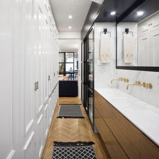 Imagen de cuarto de baño con ducha, actual, de tamaño medio, con armarios con paneles lisos, puertas de armario marrones, combinación de ducha y bañera, baldosas y/o azulejos blancos, paredes blancas, suelo de madera en tonos medios, lavabo integrado, suelo beige, ducha con puerta corredera y encimeras blancas