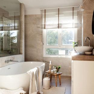 Imagen de cuarto de baño principal, tradicional renovado, de tamaño medio, con bañera exenta, baldosas y/o azulejos beige, lavabo sobreencimera y suelo beige