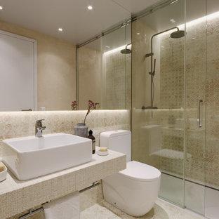 Modelo de cuarto de baño con ducha, único y flotante, actual, de tamaño medio, con puertas de armario beige, ducha empotrada, sanitario de una pieza, lavabo sobreencimera, suelo beige, ducha con puerta corredera y encimeras beige