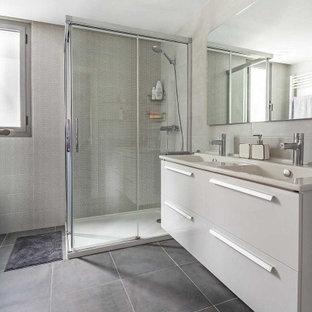 Imagen de cuarto de baño con ducha, actual, grande, con armarios con paneles lisos, puertas de armario blancas, ducha esquinera, baldosas y/o azulejos grises, baldosas y/o azulejos de porcelana, suelo de baldosas de porcelana, lavabo integrado, suelo gris, ducha con puerta con bisagras y encimeras beige