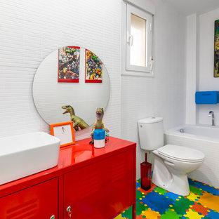 Imagen de cuarto de baño infantil, actual, con armarios tipo mueble, puertas de armario rojas, bañera empotrada, sanitario de dos piezas, baldosas y/o azulejos blancos, paredes blancas, lavabo sobreencimera, suelo multicolor y encimeras rojas