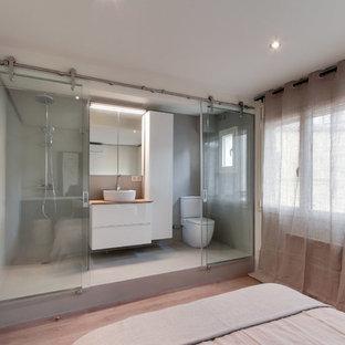 Diseño de cuarto de baño con ducha, actual, de tamaño medio, con armarios con paneles lisos, puertas de armario blancas, ducha a ras de suelo, sanitario de dos piezas, paredes grises, suelo de cemento, lavabo sobreencimera y encimera de madera