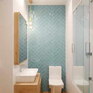 На фото: со средним бюджетом маленькие ванные комнаты в скандинавском стиле с светлыми деревянными фасадами, синей плиткой, керамической плиткой, белыми стенами, столешницей из дерева, душем с раздвижными дверями, плоскими фасадами, ванной в нише, душем над ванной, унитазом-моноблоком, паркетным полом среднего тона, душевой кабиной, настольной раковиной, бежевым полом и бежевой столешницей