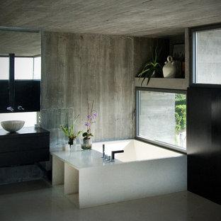 Exempel på ett stort modernt en-suite badrum, med släta luckor, skåp i mörkt trä, en jacuzzi, grå kakel, cementkakel, bänkskiva i kvartsit, en hörndusch, en toalettstol med hel cisternkåpa, ett fristående handfat, grå väggar och klinkergolv i porslin