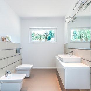 Diseño de cuarto de baño actual, grande, con armarios con paneles lisos, puertas de armario blancas, bidé, paredes blancas, suelo de baldosas de cerámica y lavabo sobreencimera