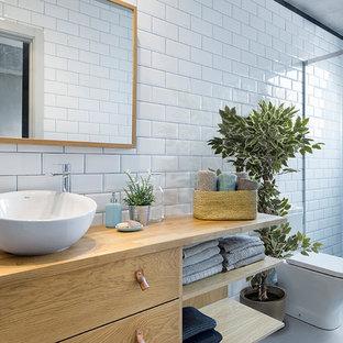 Ejemplo de cuarto de baño con ducha, industrial, de tamaño medio, con armarios con paneles lisos, puertas de armario de madera oscura, ducha empotrada, sanitario de dos piezas, baldosas y/o azulejos blancos, baldosas y/o azulejos de cemento, lavabo sobreencimera y encimera de madera