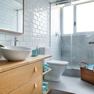 Diseño de cuarto de baño con ducha, urbano, con armarios con paneles lisos, puertas de armario de madera clara, ducha empotrada, sanitario de dos piezas, baldosas y/o azulejos blancos, baldosas y/o azulejos de cemento, paredes blancas, suelo de cemento, lavabo sobreencimera, encimera de madera y suelo gris