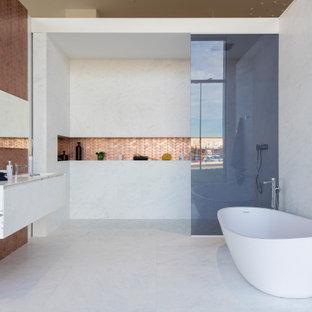 Foto de cuarto de baño actual con armarios con paneles lisos, puertas de armario blancas, bañera exenta, ducha a ras de suelo, baldosas y/o azulejos blancos, suelo blanco, ducha abierta y encimeras blancas