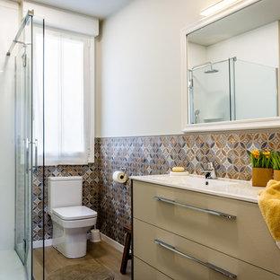 Modelo de cuarto de baño con ducha, contemporáneo, pequeño, con armarios con paneles lisos, puertas de armario beige, ducha esquinera, sanitario de dos piezas, paredes blancas, lavabo integrado, ducha con puerta con bisagras, encimeras blancas, baldosas y/o azulejos azules, baldosas y/o azulejos marrones y suelo marrón