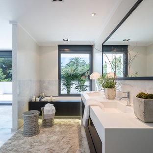 Diseño de cuarto de baño principal, actual, grande, con armarios con paneles lisos, baldosas y/o azulejos blancos, paredes blancas, lavabo integrado, puertas de armario de madera en tonos medios y bañera encastrada sin remate