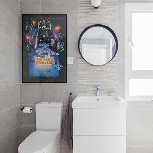 Diseño de cuarto de baño infantil, escandinavo, con puertas de armario blancas, baldosas y/o azulejos grises, baldosas y/o azulejos multicolor, armarios con paneles lisos, sanitario de dos piezas, azulejos en listel, paredes grises y suelo gris
