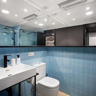 Diseño de cuarto de baño con ducha, actual, con armarios abiertos, puertas de armario negras, ducha a ras de suelo, baldosas y/o azulejos azules, paredes azules, ducha abierta, sanitario de una pieza, lavabo tipo consola y suelo beige