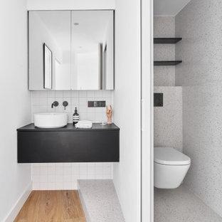 Imagen de cuarto de baño minimalista con armarios con paneles lisos, puertas de armario negras, sanitario de pared, baldosas y/o azulejos blancos, paredes blancas, suelo de madera en tonos medios, lavabo sobreencimera, suelo marrón y encimeras negras