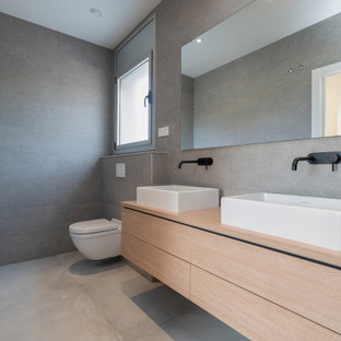 This is an example of a mid-sized contemporary 3/4 bathroom in Barcelona with recessed-panel cabinets, brown cabinets, an alcove tub, a shower/bathtub combo, a wall-mount toilet, gray tile, ceramic tile, grey walls, ceramic floors, a vessel sink, wood benchtops, grey floor, an open shower, brown benchtops, an enclosed toilet, a single vanity, a built-in vanity, wallpaper and panelled walls.