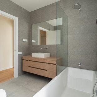Пример оригинального дизайна: ванная комната среднего размера в современном стиле с фасадами с утопленной филенкой, коричневыми фасадами, ванной в нише, душем над ванной, инсталляцией, серой плиткой, керамической плиткой, серыми стенами, полом из керамической плитки, душевой кабиной, настольной раковиной, столешницей из дерева, серым полом, открытым душем, коричневой столешницей, унитазом, тумбой под одну раковину, встроенной тумбой, потолком с обоями и панелями на части стены