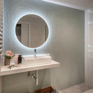 Ejemplo de cuarto de baño con ducha, actual, con armarios abiertos, puertas de armario blancas, baldosas y/o azulejos verdes, baldosas y/o azulejos en mosaico, suelo de baldosas de cerámica, lavabo sobreencimera, suelo gris, ducha abierta y encimeras blancas