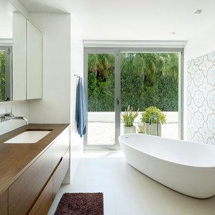 Ejemplo de cuarto de baño principal, actual, con armarios con paneles lisos, bañera exenta, paredes blancas, lavabo bajoencimera, encimera de madera, puertas de armario de madera oscura y baldosas y/o azulejos multicolor