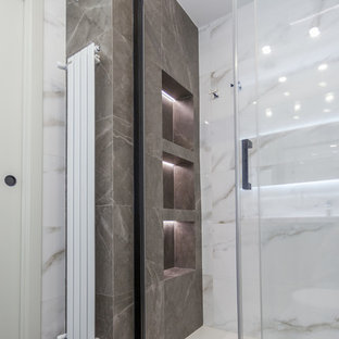 Inspiration for a mid-sized 3/4 porcelain floor, gray floor and tray ceiling bathroom remodel in Valencia with a one-piece toilet, an integrated sink, white countertops and a niche