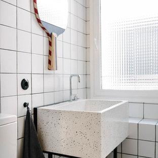 Inredning av ett modernt badrum med dusch, med öppna hyllor, vit kakel, bänkskiva i terrazo, vitt golv, vita väggar och ett konsol handfat