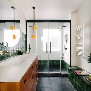 Ejemplo de cuarto de baño con ducha, actual, con puertas de armario de madera oscura, paredes blancas, suelo negro, ducha con puerta corredera, encimeras blancas, armarios tipo mueble, ducha empotrada, baldosas y/o azulejos verdes y lavabo de seno grande