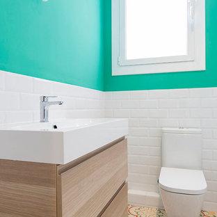 Foto di una stanza da bagno padronale scandinava di medie dimensioni con ante lisce, ante in legno scuro, vasca ad alcova, vasca/doccia, WC a due pezzi, pareti verdi, pavimento con piastrelle in ceramica e lavabo integrato