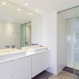 Modelo de cuarto de baño contemporáneo con armarios con paneles lisos, puertas de armario blancas, ducha empotrada, sanitario de pared, paredes blancas, lavabo sobreencimera, suelo gris, ducha con puerta corredera y encimeras blancas