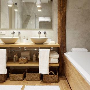 Foto de cuarto de baño principal, actual, de tamaño medio, con armarios abiertos, puertas de armario de madera oscura, bañera empotrada, combinación de ducha y bañera, lavabo sobreencimera, encimera de madera y encimeras beige