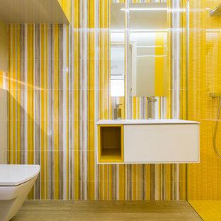 Imagen de cuarto de baño con ducha, minimalista, de tamaño medio, con armarios con paneles lisos, puertas de armario blancas, ducha a ras de suelo, sanitario de pared, paredes amarillas, suelo de madera en tonos medios y lavabo integrado