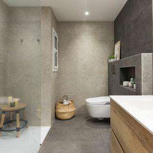 Ejemplo de cuarto de baño con ducha, escandinavo, con armarios con paneles lisos, puertas de armario de madera oscura, ducha a ras de suelo, sanitario de pared, baldosas y/o azulejos beige, baldosas y/o azulejos grises, lavabo integrado, suelo gris, ducha abierta y encimeras blancas