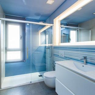 Diseño de cuarto de baño principal, marinero, de tamaño medio, con armarios con paneles lisos, puertas de armario blancas, ducha empotrada, sanitario de pared, paredes multicolor, suelo de baldosas de cerámica, lavabo integrado, baldosas y/o azulejos multicolor y baldosas y/o azulejos de cerámica