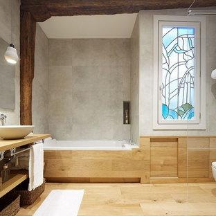 Foto de cuarto de baño contemporáneo con armarios con paneles lisos, bañera encastrada, ducha abierta, sanitario de pared, baldosas y/o azulejos grises, paredes beige, suelo de madera clara, lavabo sobreencimera, encimera de madera, suelo marrón, ducha con puerta corredera y encimeras marrones