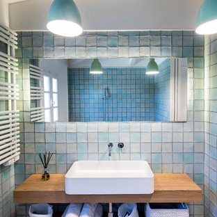 Coastal bathroom with open cabinets, medium wood cabinets, blue tiles, blue walls, terracotta flooring, a vessel sink, wooden worktops and red floors.