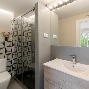 Ejemplo de cuarto de baño con ducha, actual, con armarios con paneles lisos, puertas de armario de madera clara, ducha esquinera, baldosas y/o azulejos grises, baldosas y/o azulejos multicolor, paredes blancas, lavabo integrado, suelo gris, ducha con puerta corredera y encimeras blancas