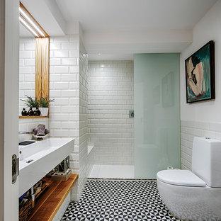 Стильный дизайн: ванная комната среднего размера в современном стиле с писсуаром, белой плиткой, белыми стенами, душевой кабиной и раковиной с несколькими смесителями - последний тренд