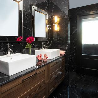 Ejemplo de cuarto de baño principal, tradicional renovado, con puertas de armario de madera en tonos medios, baldosas y/o azulejos negros, lavabo sobreencimera, suelo negro, armarios con paneles empotrados, paredes negras y encimeras negras