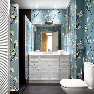 Modelo de cuarto de baño con ducha, tradicional renovado, con puertas de armario blancas, armarios con puertas mallorquinas, ducha empotrada, sanitario de una pieza, baldosas y/o azulejos negros, paredes multicolor, suelo negro, ducha abierta y encimeras blancas