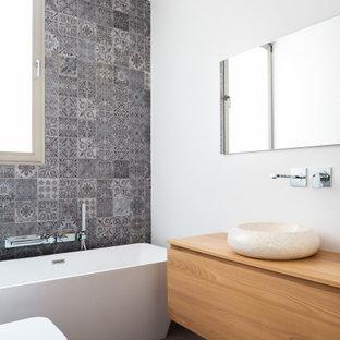 Foto de cuarto de baño con ducha, actual, de tamaño medio, con armarios con paneles lisos, puertas de armario de madera oscura, bañera exenta, sanitario de pared, baldosas y/o azulejos grises, paredes blancas, lavabo sobreencimera, encimera de madera, suelo gris y encimeras beige