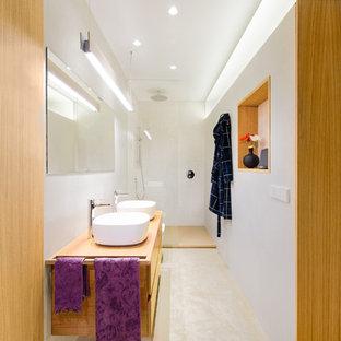 Imagen de cuarto de baño con ducha, contemporáneo, con armarios con paneles lisos, puertas de armario de madera oscura, ducha empotrada, baldosas y/o azulejos blancos, paredes blancas, lavabo sobreencimera, encimera de madera y suelo beige