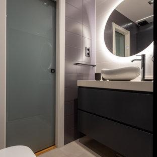 Modelo de cuarto de baño con ducha, contemporáneo, de tamaño medio, con armarios con paneles lisos, puertas de armario negras, sanitario de pared, baldosas y/o azulejos grises, baldosas y/o azulejos de porcelana, suelo de baldosas de porcelana, lavabo sobreencimera, suelo gris y encimeras grises