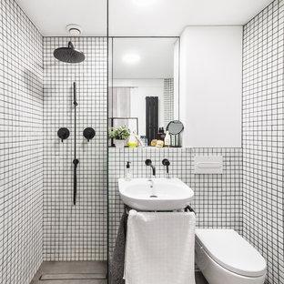 Foto de cuarto de baño con ducha, contemporáneo, pequeño, con ducha a ras de suelo, sanitario de pared, paredes blancas, suelo de cemento, lavabo suspendido y suelo gris