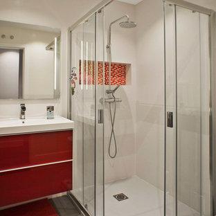 Idéer för att renovera ett mellanstort funkis badrum för barn, med en hörndusch, grå kakel, porslinskakel, vita väggar, klinkergolv i porslin, ett avlångt handfat, släta luckor och röda skåp