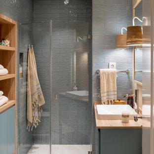 Неиссякаемый источник вдохновения для домашнего уюта: главная ванная комната среднего размера в скандинавском стиле с стеклянными фасадами, белыми фасадами, душем без бортиков, инсталляцией, синей плиткой, керамической плиткой, желтыми стенами, полом из керамической плитки, настольной раковиной, столешницей из ламината, синим полом, душем с распашными дверями, коричневой столешницей, нишей, тумбой под одну раковину и встроенной тумбой