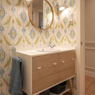 Foto de cuarto de baño actual con puertas de armario de madera oscura, encimeras blancas, paredes multicolor, suelo de madera en tonos medios, encimera de madera, suelo marrón, armarios con paneles lisos y lavabo encastrado