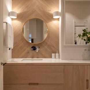 На фото: большая ванная комната в современном стиле с фасадами цвета дерева среднего тона, белой столешницей, бежевой плиткой, керамогранитной плиткой, бежевыми стенами, полом из ламината, врезной раковиной, мраморной столешницей, коричневым полом и плоскими фасадами с