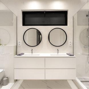 Imagen de cuarto de baño con ducha, actual, con armarios con paneles lisos, ducha a ras de suelo, sanitario de pared, baldosas y/o azulejos blancos, paredes blancas, lavabo integrado, encimeras blancas, puertas de armario blancas y suelo blanco