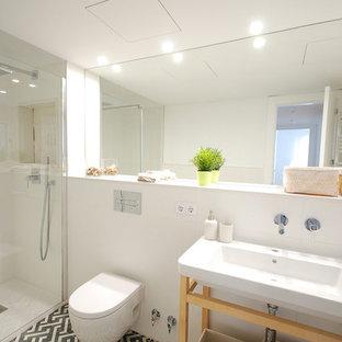 Foto de cuarto de baño con ducha, contemporáneo, de tamaño medio, con armarios abiertos, puertas de armario de madera clara, sanitario de pared, paredes blancas, encimeras blancas, ducha empotrada, baldosas y/o azulejos blancos, lavabo integrado y suelo multicolor