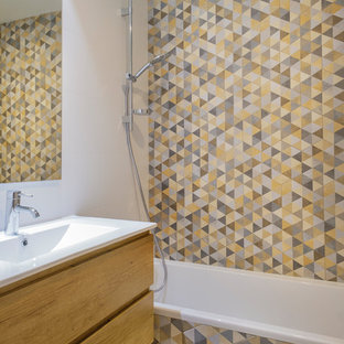 Photo of a contemporary master bathroom in Other with flat-panel cabinets, light wood cabinets, an alcove tub, a shower/bathtub combo, gray tile, yellow tile, white walls, mosaic tile floors, an integrated sink, multi-coloured floor and white benchtops.
