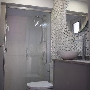 Immagine di una piccola stanza da bagno con doccia con ante grigie, doccia alcova, WC sospeso, piastrelle grigie, pareti bianche, pavimento con piastrelle in ceramica, lavabo a bacinella, top alla veneziana, pavimento grigio, porta doccia scorrevole e top grigio